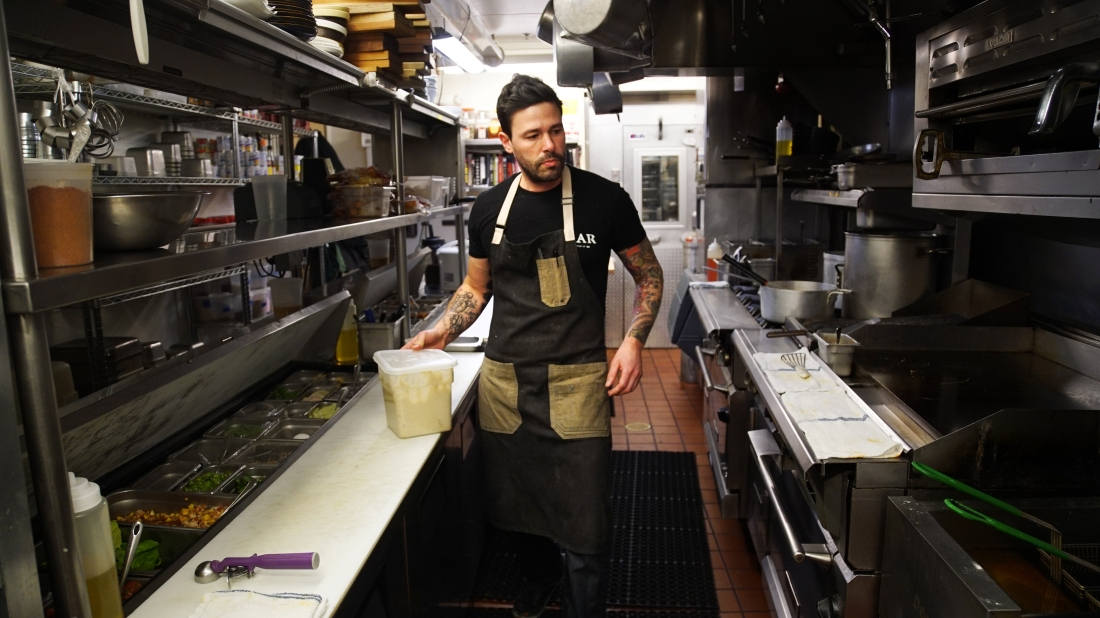 "Jesse Miller prepares a dish Feb. 16 in the kitchen at Bar Pilar, a restaurant on 14th Street in Washington, D.C. Miller's kitchen staff, all immigrants, went on strike Thursday during a ""Day Without Immigrants,"" a nationwide protest against President Donald Trump's recent action on immigration."