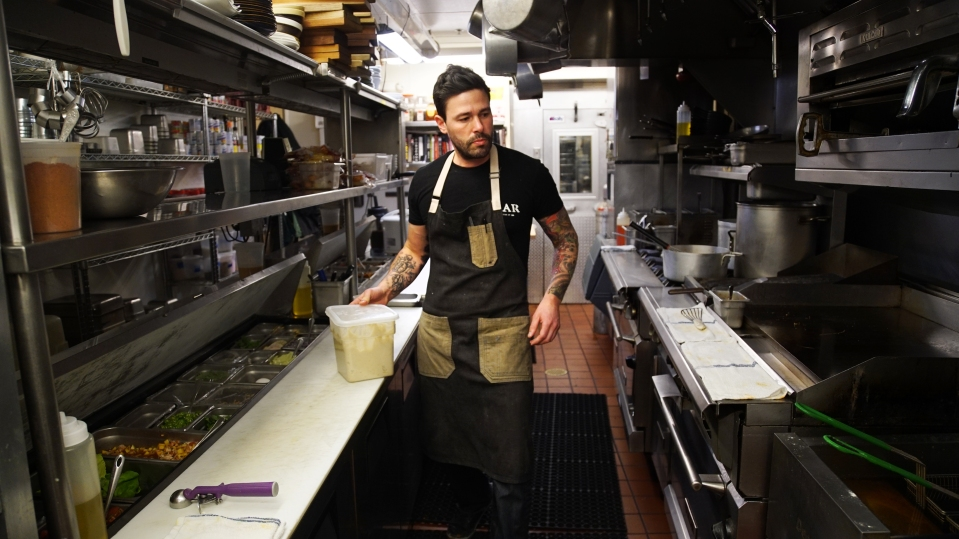 """Jesse Miller prepares a dish Feb. 16 in the kitchen at Bar Pilar, a restaurant on 14th Street in Washington, D.C. Miller's kitchen staff, all immigrants, went on strike Thursday during a """"Day Without Immigrants,"""" a nationwide protest against President Donald Trump's recent action on immigration."""